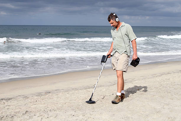 A man using his metal detector on the beach.